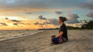Woman sits and meditates on the beach at sunrise